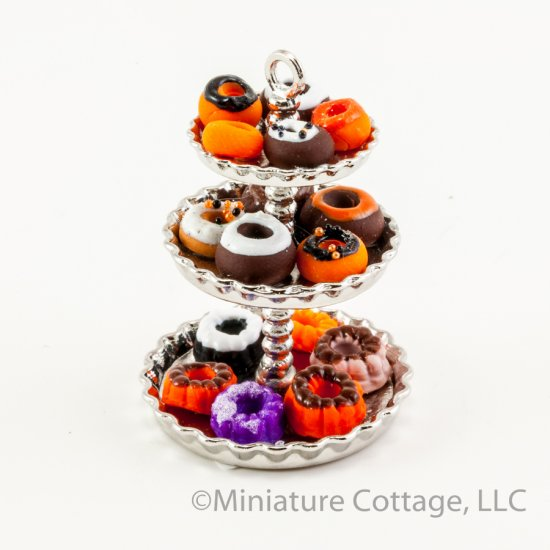 three tiered serving tray with halloween donuts and cakes
